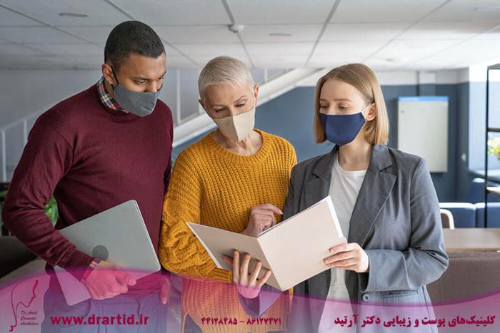 people work wearing medical masks - مراقبت از پوست در زمان پاندامی ویروس کرونا